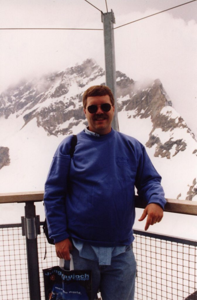 A person standing on top of a snow covered mountain  Description automatically generated